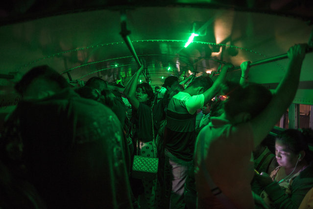 """In this March 21, 2017 photo, people stand in a bus waiting to go home after their work day at a """"maquiladora"""" for car accessories in Matamoros, Tamaulipas state, Mexico, across the border from Brownsville, Texas. (Photo by Rodrigo Abd/AP Photo)"""