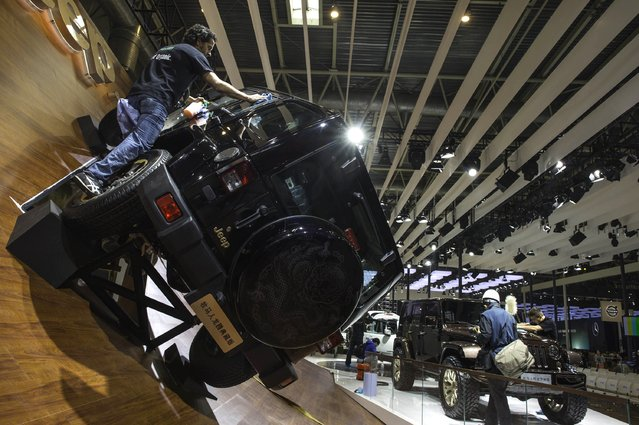 """This picture taken on April 19, 2014 shows a staff installing a Jeep car model in an exhibition hall of the China International Exhibition Center , ahead of the """"Auto China 2014"""" Beijing International Automotive Exhibition in Beijing. (Photo by AFP Photo)"""