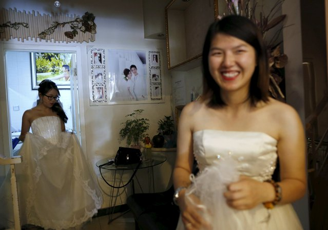 Li Tingting (R) smiles as she waits for her partner Teresa at a bridal photography studio while meeting the media in Beijing, China July 2, 2015. (Photo by Kim Kyung-Hoon/Reuters)