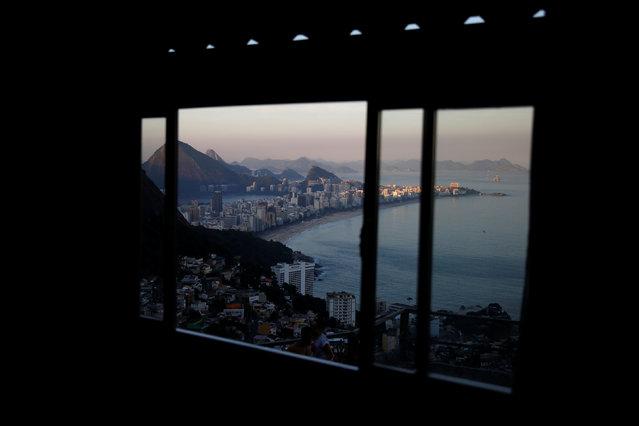 Ipanema beach is seen through a window at the Alto Vidigal hostel in Vidigal favela, in Rio de Janeiro, Brazil, April 23, 2016. (Photo by Pilar Olivares/Reuters)