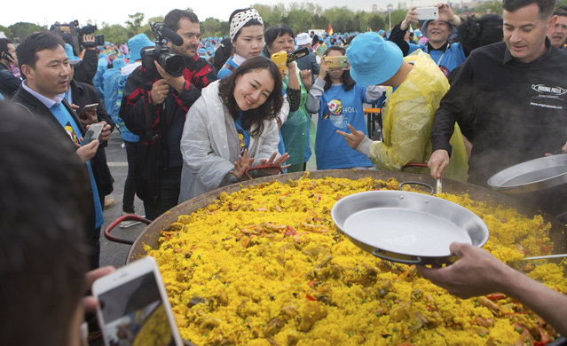 Chinese conglomerate Tiens Group employees take photos while waiting to be served Paella in Madrid, Spain, Friday, May 6, 2016. (Photo by Paul White/AP Photo)