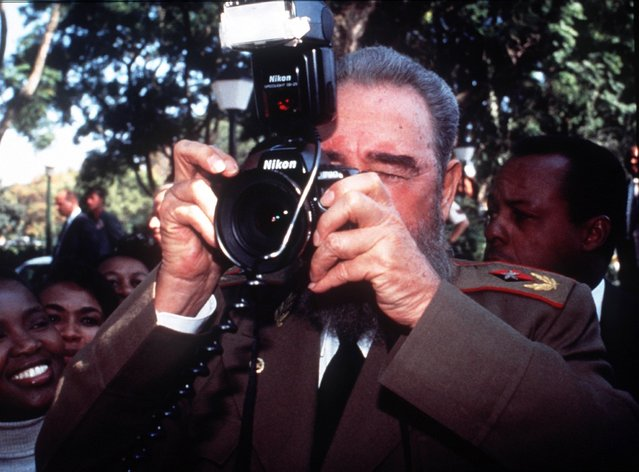 In this May 10, 1994 file photo, Cuban leader Fidel Castro briefly uses the camera of photojournalist Desmond Boylan outside the president's residence as he leaves for the inauguration ceremony for South Africa's first black President Nelson Mandela, in Pretoria, South Africa. (Photo by Gary Bernard/AP Photo)
