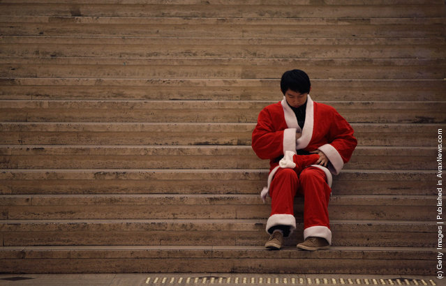 South Koreans wear Santa Claus outfits and hold gifts to promote Christmas at a charity event