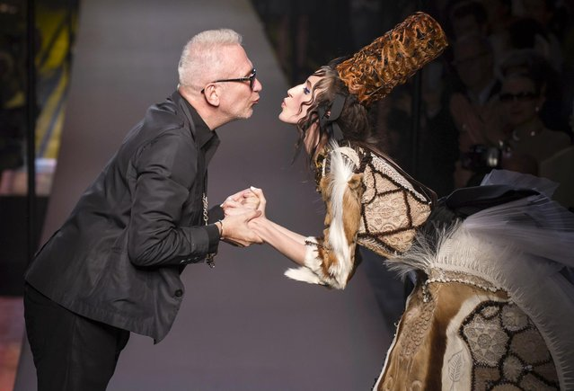 French designer Jean Paul Gaultier and a model wearing one of his creation are about to kiss during the presentation of his fall-winter 2015/2016 Haute Couture fashion collection, in Paris, France, Wednesday, July 8, 2015. (Photo by Kamil Zihnioglu/AP Photo)