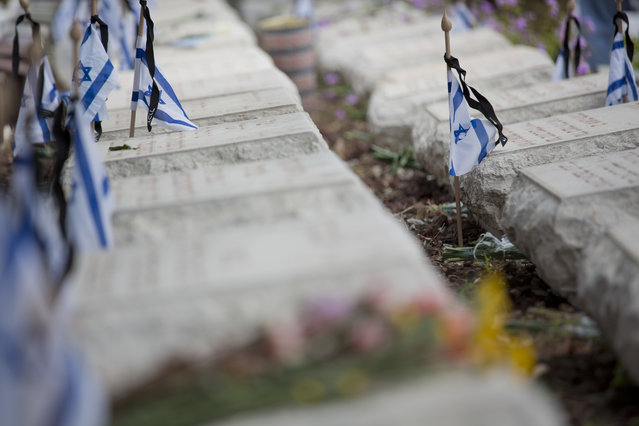Israeli small flags with black ribbons are placed on the graves of fallen soldiers on the eve of memorial Day in Kiryat Shaul military cemetery in Tel Aviv, Israel, Tuesday, May 10, 2016. (Photo by Ariel Schalit/AP Photo)