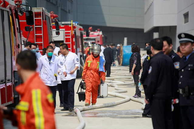 Firefighters and police are seen near the site of a fire at the Shanghai Hongqiao Airport in Shanghai April 29, 2016. (Photo by Reuters/China Daily)