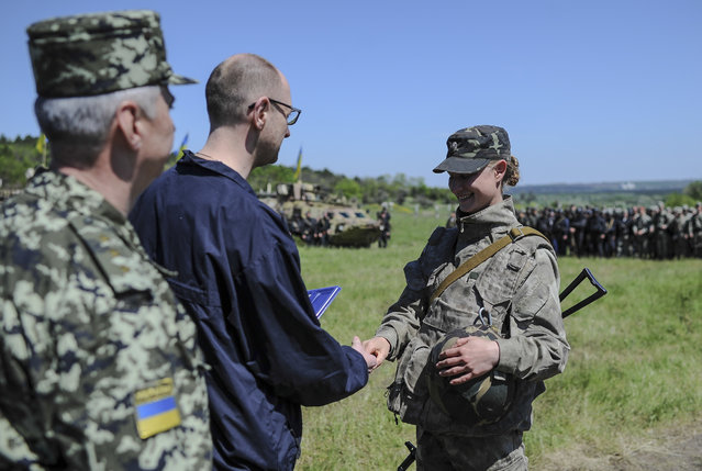 Ukrainian Prime Minister Arseniy Yatsenyuk, center, shake hands with a Ukrainian soldier at a block post on the road at Slovyansk, Ukraine, Wednesday, May 7, 2014. Ukrainian military operations that began Monday to expunge pro-Russia forces from the city of Slovyansk were the interim government's most ambitious effort so far to quell weeks of unrest in Ukraine's mainly Russian-speaking east. (Photo by Andrew Kravchenko/AP Photo)