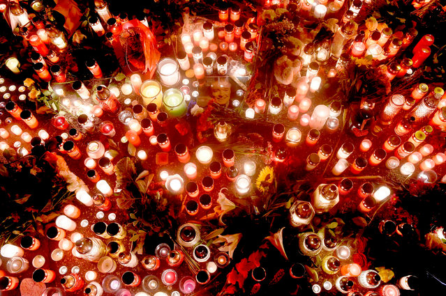 """A photo of Czech singer Karel Gott is placed inmid candles in front of his house on October 02, 2019 in Prague. Czech pop singer Karel Gott, who was a particular favourite in neighbouring Germany where media once dubbed him the """"Sinatra of the East"""", died at 80, his family said on October 2, 2019. (Photo by Michal Cizek/AFP Photo)"""