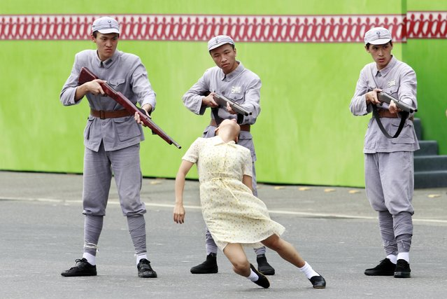 Performers re-enact the 1947 massacre of Taiwanese intellectuals by mainland China's Nationalists troops during the inauguration ceremony of Taiwan's President Tsai Ing-wen in Taipei, Taiwan, Friday, May 20, 2016. Taiwan inaugurated Tsai as its first female president on Friday, returning the pro-independence Democratic Progressive Party to power amid new concerns over increasingly fractious relations with Beijing and a flagging economy. (Photo by Chiang Ying-ying/AP Photo)