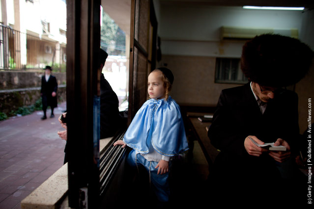 A boy looks out of a window as Ultra Orthodox Jews celebrate the Jewish holiday of Purim