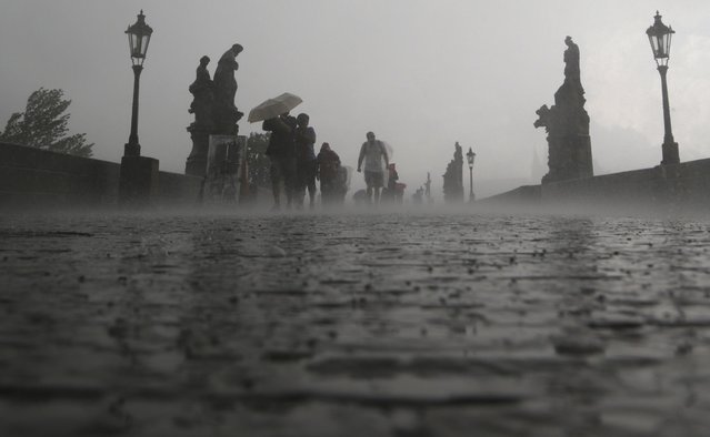 People cross the medieval Charles Bridge during a storm in Prague, Czech Republic, Tuesday, May 31, 2016. Prague as well as other European cities was hit by heavy thunderstorm on Tuesday. (Photo by Petr David Josek/AP Photo)