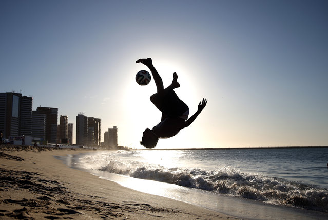 A local boy plays football on Iracema Beach on June 11, 2014 in Fortaleza, Brazil. (Photo by Robert Cianflone/Getty Images)