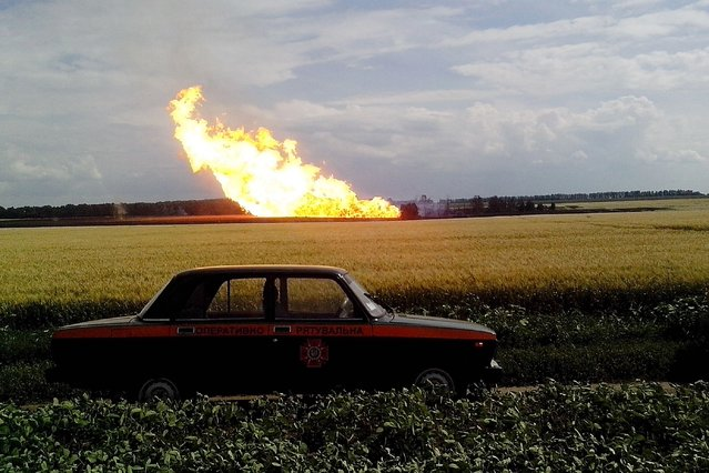 This handout picture taken and released by the Ukrainian Emergency Service on June 17, 2014 shows a police car parked beside a field near a fire on the gas pipeline the village of Iskivtsi in the Lokhvytsia region. A blast hit a major Ukrainian pipeline on June 16 used to transport Russian natural gas to European clients, Ukrainian police officials said. (Photo by AFP Photo/Urkainian Emergency Press-Service)