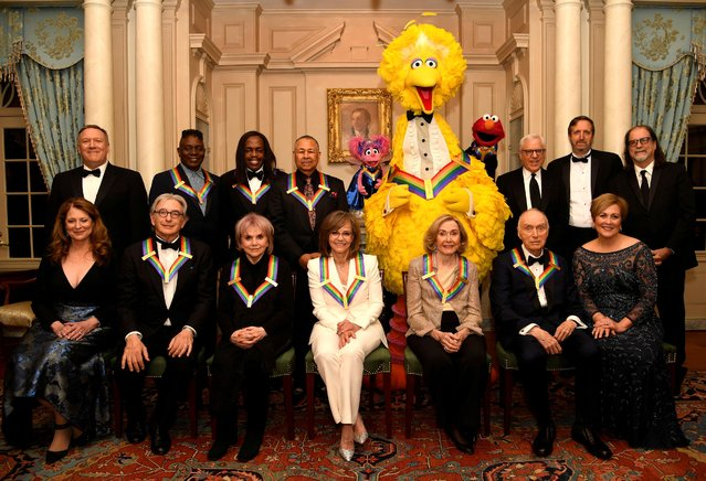 2019 Kennedy Center Honorees gather for a group photo (seated, L-R) Susan Pompeo, conductor Michael Tilson Thomas, singer Linda Ronstadt, actress Sally Field, Sesame Street co-founders Joan Ganz Cooney and Dr. Lloyd Morrisette and Kennedy Center President Deborah F. Rutter,(standing, L-R) Secretary of State Mike Pompeo, Earth, Wind & Fire band members Philip Bailey, Verdine White and Ralph Johnson and Sesame Street characters Abby, Big Bird and Elmo, and Kennedy Center producers Ricky Kirschner and Glenn Weiss, after a gala dinner at the U.S. State Department, in Washington, U.S., December 7, 2019. (Photo by Mike Theiler/Reuters)