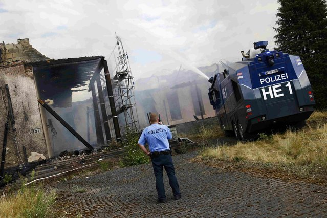 Police use a water cannon to help firefighters to extinguish a fire which broke out at a former U.S. airfield in Erlensee, Germany July 30, 2015. (Photo by Kai Pfaffenbach/Reuters)