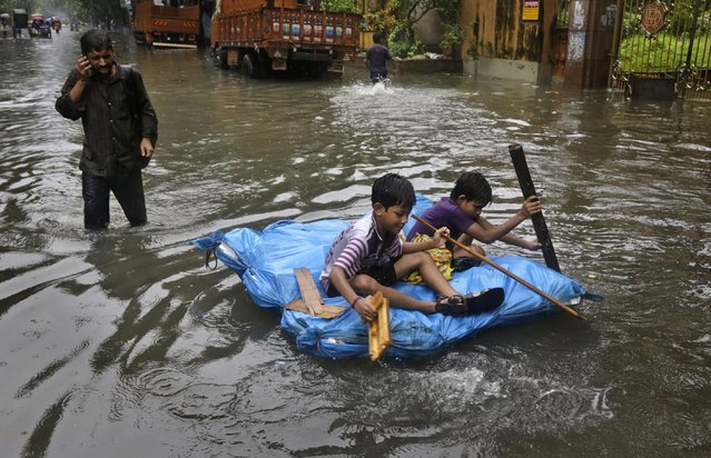 Indian children play on a water logged street in Kolkata, India, Saturday, August 1, 2015. Cyclonic storm Komen weakened into a depression after making landfall over Bangladesh coast on Thursday, causing heavy rainfall in several parts of the eastern Indian state of West Bengal and throwing normal life out of gear as most parts of the city were submerged, according to local reports. (Photo by Bikas Das/AP Photo)