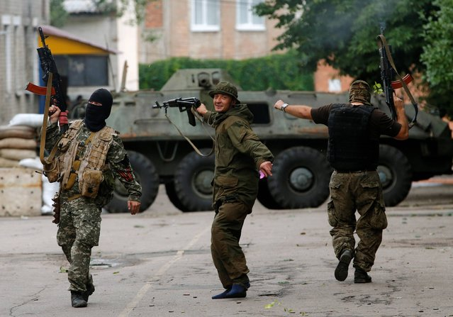 "Pro-Russian fighters dance and fire in the air in an Ukrainian military unit captured by pro-Russian fighters in the city of Donetsk, eastern Ukraine, Friday, June 27, 2014. ""Donetsk People's Republic's"" fighters captured the Ukrainian military unit in Donetsk on Thursday, June 26. (Photo by Dmitry Lovetsky/AP Photo)"