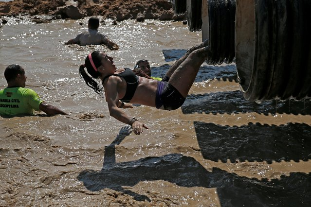 Participants compete in the Mud Day Race extreme run competition at El Goloso military base, outside Madrid, Spain, June 11, 2016. (Photo by Juan Medina/Reuters)