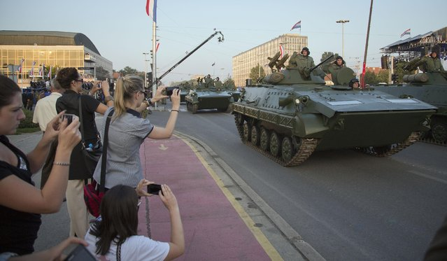 "Attendants take photographs of military vehicles during a military parade marking the 20th anniversary of the ""Operation Storm"" that crushed Serb insurgency in Croatia, in Zagreb, Tuesday, August 4, 2015. (Photo by Darko Bandic/AP Photo)"