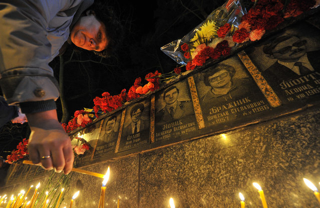 A man lights a candle at the monument to Chernobyl victims in Slavutich, some 50 kilometres (30 miles) from the accident site, and where many of the power station's personnel used to live, during a memorial ceremony