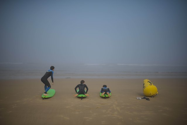 Surfers practice their technique in the early morning fog on Mallipo beach near Taean on June 29, 2014. South Korea's beach season picks up in July and August to coincide with the annual school holidays. (Photo by Ed Jones/AFP Photo)