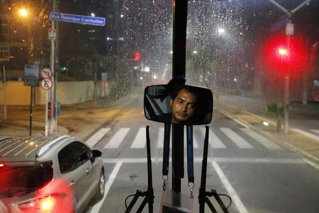 """The media bus driver is reflected in a mirror during the trip away from the Pernambuco arena in the rain in Recife June 28, 2014. In a project called """"On The Sidelines"""" Reuters photographers share pictures showing their own quirky and creative view of the 2014 World Cup in Brazil. (Photo by Brian Snyder/Reuters)"""