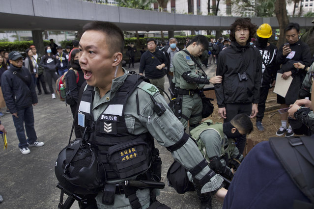 Riot police perform body search on a man ahead of a rally demanding electoral democracy and call for boycott of the Chinese Communist Party and all businesses seen to support it in Hong Kong, Sunday, January 19, 2020. Hong Kong has been wracked by often violent anti-government protests since June, although they have diminished considerably in scale following a landslide win by opposition candidates in races for district councilors late last year. (Photo by Ng Han Guan/AP Photo)