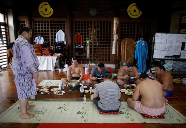 Mongolian-born Tomozuna Oyakata (3rd L), or master of the Tomozuna stable, and his wrestlers eat a meal inside the main hall of Ganjoji Yakushido temple in Nagoya, Japan on July 18, 2017. With rare permission granted by sumo's governing body, Reuters was able to observe the stable's wrestlers training at their temporary Buddhist temple base for the Nagoya Grand Sumo Tournament that kicked off last week, gaining insight into the intricacies of sumo. (Photo by Issei Kato/Reuters)