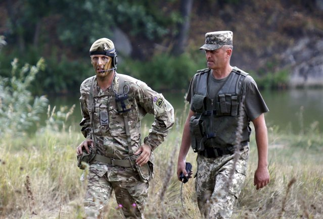 A British military instructor (L) and a Ukrainian army officer walk as they inspect a military drill at a shooting range near Zhytomyr, Ukraine, August 11, 2015. (Photo by Valentyn Ogirenko/Reuters)