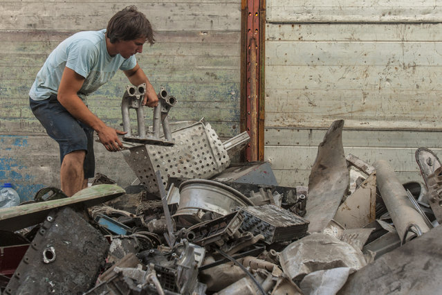 "Danilo Baletic, 22, picks scrap metal parts to make sculptures, at a junkyard in Podgorica July 20, 2014. Baletic makes sculptures of his childhood cartoon heroes, ""Transformers"", from scrap metal. In the last two years he has made seven ""Transformers"" sculptures that are placed on the streets of Montenegro's capital Podgorica as part of an exhibition called ""Transformers defending Podgorica"". (Photo by Stevo Vasiljevic/Reuters)"