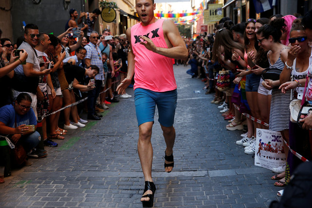 A competitor runs as he takes part in the annual race on high heels during Gay Pride celebrations in the quarter of Chueca in Madrid, Spain, June 30, 2016. (Photo by Susana Vera/Reuters)