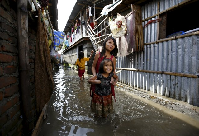 Children walk along an alley filled with floodwaters caused by heavy rainfall flowing from the swollen Bagmati River in a slum in Kathmandu, Nepal August 17, 2015. (Photo by Navesh Chitrakar/Reuters)