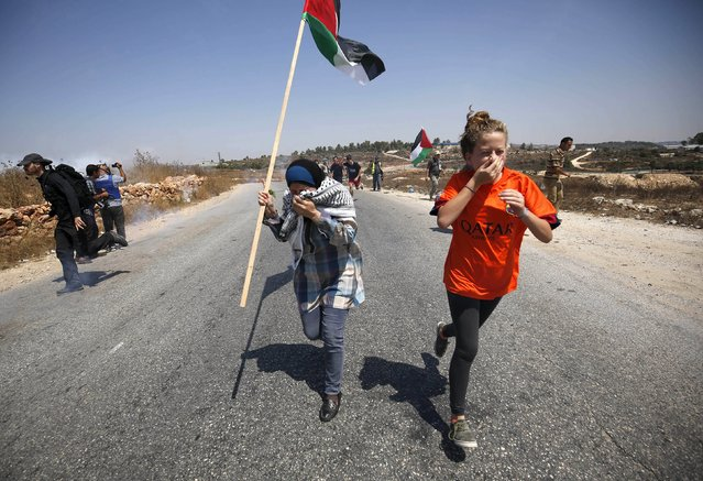 Protesters react as they run away from tear gas fired by Israeli troops during clashes at a protest against Jewish settlements in the West Bank village of Nabi Saleh, near Ramallah August 21, 2015. (Photo by Mohamad Torokman/Reuters)