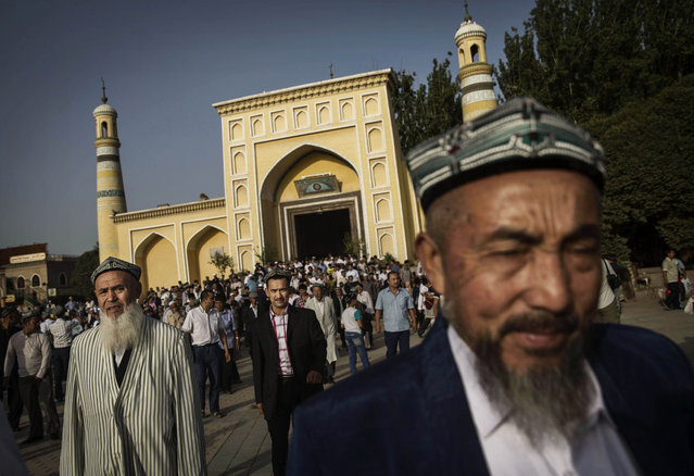 Uyghur men leave the Id Kah Mosque following the Eid prayers on July 29, 2014 in old Kashgar, Xinjiang Province, China. (Photo by Kevin Frayer/Getty Images)
