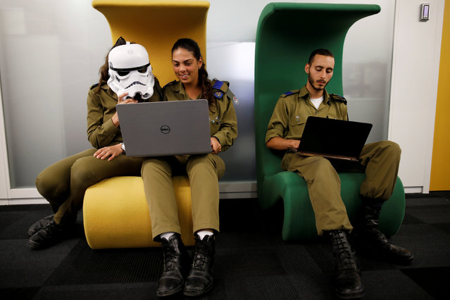Israeli soldiers, one wearing a Star Wars Storm Trooper Voice Changing Helmet, work on laptops as they take part in a cyber security training course, called a Hackathon, at iNT Institute of Technology and Innovation, at a high-tech park in Beersheba, southern Israel August 28, 2017. (Photo by Amir Cohen/Reuters)