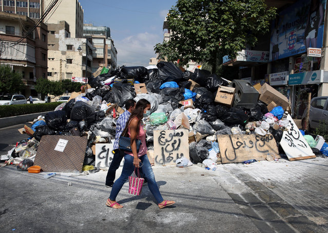 Lebanese citizens pass a pile of garbage blocking a street in the town of Jal el-Dib east Beirut, Lebanon, Wednesday, August 26, 2015. Protests continued Wednesday over the country's worsening garbage collection crisis. (Photo by Bilal Hussein/AP Photo)
