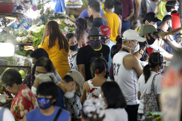 Men wearing protective mask buys food as people rush before the Munoz market closes for it's morning business as they cut their operations to four hours a day as part the enhanced community quarantine to prevent the spread of the new coronavirus in Metro Manila, Philippines on Thursday, March 19, 2020. (Photo by Aaron Favila/AP Photo)