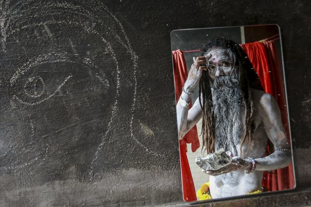 A Naga sadhu, or a Hindu holy man, applies ash at his camp before a procession during Kumbh Mela or the Pitcher Festival in Trimbakeshwar, India, August 27, 2015. (Photo by Danish Siddiqui/Reuters)