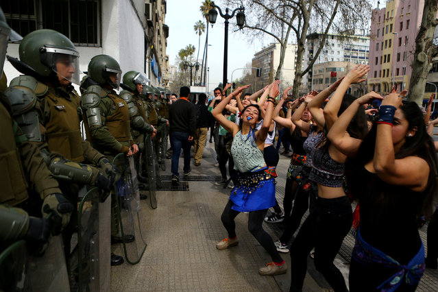 Demonstrators perform a dance in front of riot policemen during a march called by students to request changes in the education system in Santiago, Chile September 5, 2017. (Photo by Ivan Alvarado/Reuters)