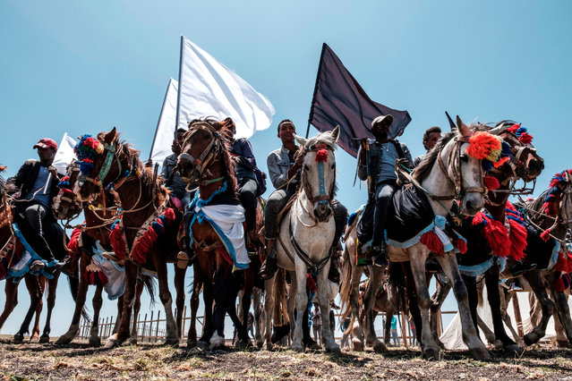 Horsemen hold black and white flags during a memorial ceremony at the crash site of the Ethiopian Airlines Flight 302 airplane accident in Tulu Fara, Ethiopia, on March 8, 2020. Ethiopian Airlines Flight 302 crashed southeast of Addis Ababa on March 10, 2019, killing 157 people. (Photo by Eduardo Soteras/AFP Photo)