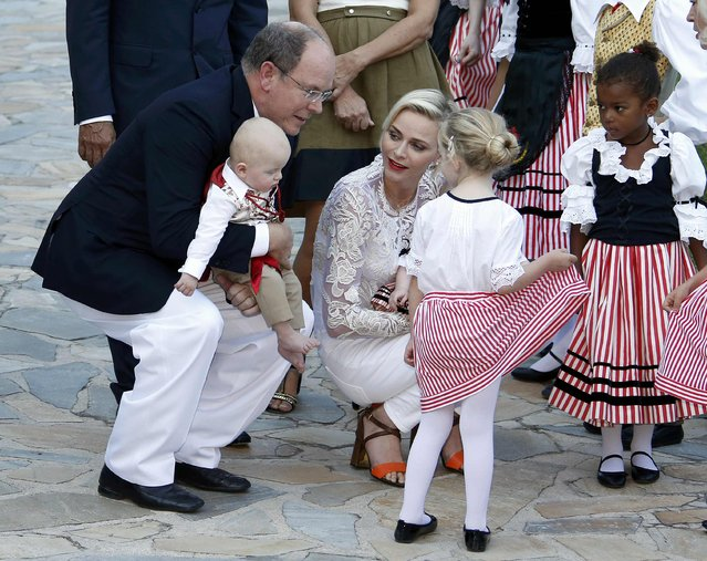 "Prince Albert II  and his wife Princess Charlene of Monaco are greeted by dancers wearing traditional costume as they arrive with their twins, Prince Jacques and Princess Gabriella (hidden), to take part in the traditional ""Pique Nique Monegasque"" (Monaco's picnic) in Monaco August 28, 2015. (Photo by Eric Gaillard/Reuters)"