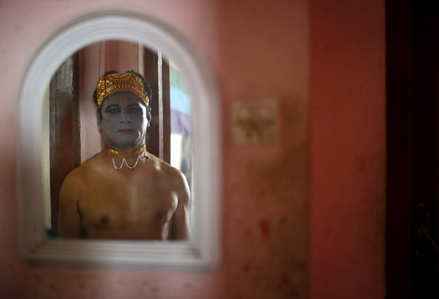 A reveller depicting Lord Krishna, a Hindu deity, is reflected in a mirror as he stands in a doorway before taking part in a LGBT (lesbian, gay, bisexual, and transgender) pride parade to mark Gaijatra Festival, also known as the festival of cows, in Kathmandu, Nepal August 30, 2015. (Photo by Navesh Chitrakar/Reuters)