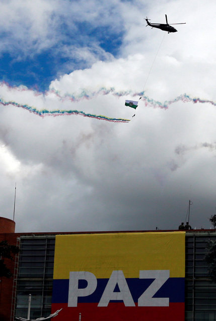 Soldiers hang on a rope holding flags as a military helicopter performs a flypast during a military parade to celebrate the 206th anniversary of Colombia's independence in Bogota, Colombia, July 20, 2016. (Photo by John Vizcaino/Reuters)