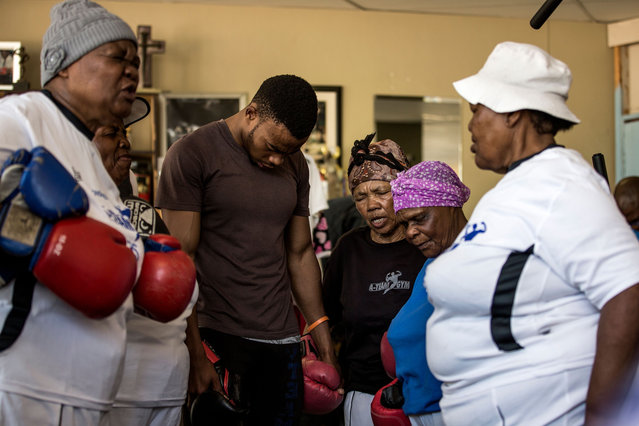 "77 year-old Gladys Ngwenya (C) and 79 year old Constance Ngubane (2R) pray with others ahead of taking part in a ""Boxing Gogos"" (Grannies) training session hosted by the A Team Gym in Cosmo City in Johannesburg on September 19, 2017. (Photo by Gulshan Khan/AFP Photo)"