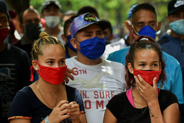 """Venezuelan migrants wear face masks as they wait to be checked by health workers to rule out the novel coronavirus as part of their repatriation process in Cali, Colombia on April 13, 2020. The Mayor of Cali, Jorge Ivan Ospina, announced Sunday a """"humanitarian corridor"""" was started to repatriate Venezuelan migrants. (Photo by Luis Robayo/AFP Photo)"""