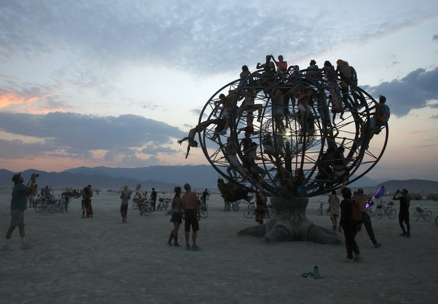 "Participants climb an the Eidolon Panspermia Ostentatia Duodenum (EPOD) art installation during the Burning Man 2014 ""Caravansary"" arts and music festival in the Black Rock Desert of Nevada, August 28, 2014. (Photo by Jim Urquhart/Reuters)"