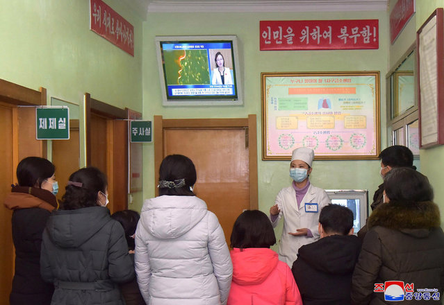 A photo released by the official North Korean Central News Agency (KCNA) shows a health worker speaking to people about the Covid-19 and coronavirus, in Pyongyang, Democratic People's Republic of Korea, 15 February 2020. (Photo by KCNA/EPA/EFE)