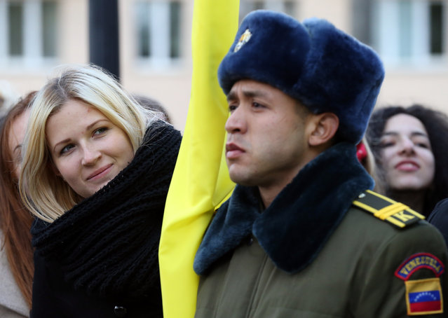 A Belarussian woman looks past a Venezuelan military school student, as President Nicolas Maduro takes part at the unveiling ceremony of a bust of Venezuela's national hero Simon Bolivar, in Minsk, Belarus, 05 October 2017. Maduro arrives from his Moscow visit to Belarus to hold talks with top officials on bilateral cooperation in housing construction, industrial development, and trade. (Photo by Tatyana Zenkovich/EPA/EFE)