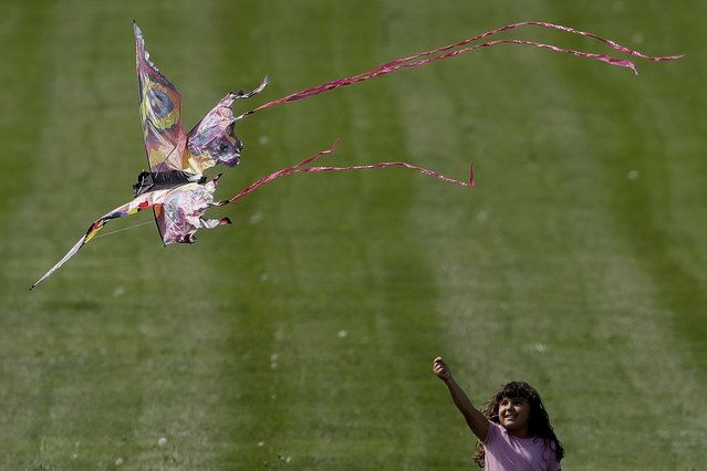 A girl flies a kite on the lawn at the Liberty Memorial after watching aircraft from nearby Whiteman Air Force base fly over Tuesday, April 28, 2020, in Kansas City, Mo. The flyover included one B-2 Spirit stealth bomber, two A-10 Thunderbolt IIs and four T-38 Talons and flew over several metro hospitals as a tribute to healthcare workers fighting COVID-19. (Photo by Charlie Riedel/AP Photo)