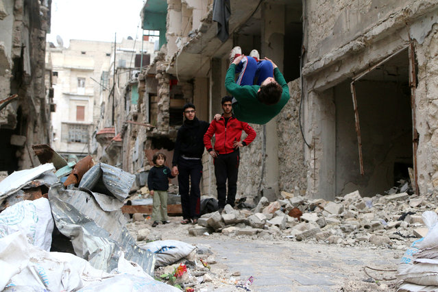 "Gymnast Ahmad al-Sawas performs gymnastic moves near damaged buildings in the rebel-held Bustan al-Qasr neighbourhood of Aleppo, Syria March 26, 2016. As Syrian gymnast Ahmad al-Sawas watched his country fall apart, his Olympic dream collapsed too. The last national champion before the fighting began, he knew that supporting the anti-government side in the five-year-old civil war would prevent him from being selected for the Rio Games. ""I chose to be an athlete who participates in the revolution"", said Ahmad, who trains where he can for two hours a day – be it on a mattress on a soccer field, in a local hall or somersaulting off a wall. (Photo by Abdalrhman Ismail/Reuters)"